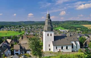 Prosoz Herten-Bild Startseite Eversberg ProBAUG- ländliche Landschaft mit Häusern und einer weißen Kirche mit Turm