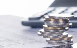 Prosoz Herten-Bild zu Corona Einmalzahlung-Vordergründig sieht man einen Stapel mit 1 und 2 € Münzen hintergründig einen Taschenrechner mit Liste